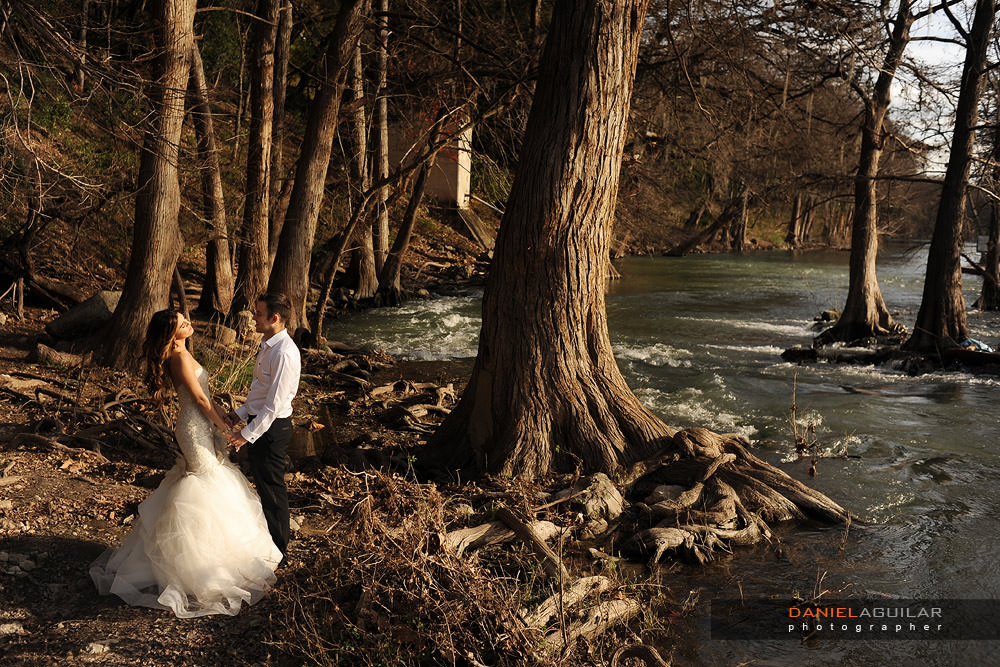 A bride and a groom holding hands at the shore of the Guadalupe River