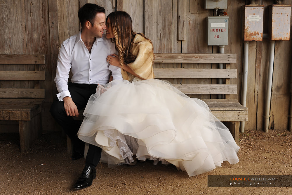 Bride and groom sitting on a bench and smiling in barn of Gruene TX